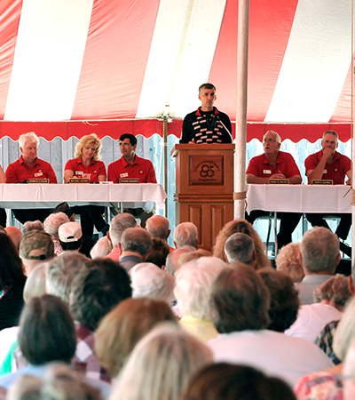 Man speaking at a podium in front of seated people