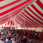 Many people sitting in a red and white striped tent
