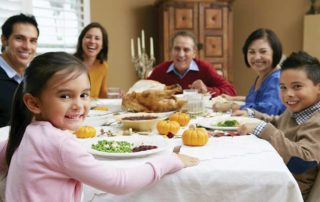 Family sitting around a table eating Thanksgiving dinner