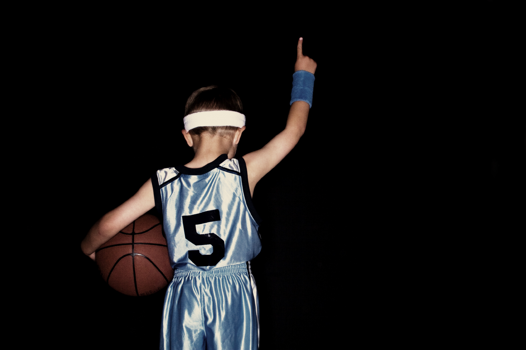 Boy in basketball gear holding a basketball and pointing his finger in the air