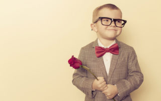 Boy in suit and glasses holding a rose