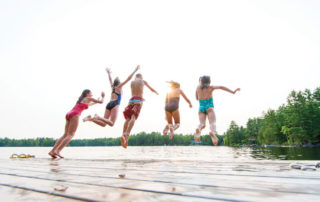 kids jumping into water from dock