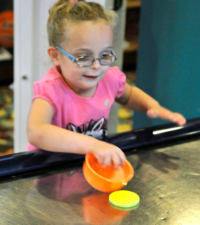 girl playing air hockey