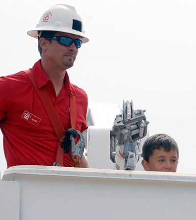 man and boy in bucket of line truck