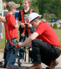 man assisting kids with lineworker gear