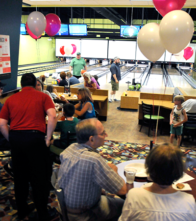 people bowling, talking, and eating