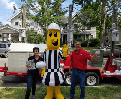 mascot, man, and woman smiling in front of electric equipment demo