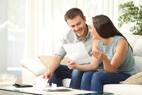 Man and woman smiling while paying bills