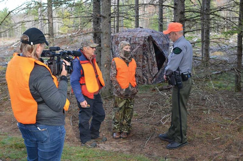two men speaking with DNR officer while being filmed
