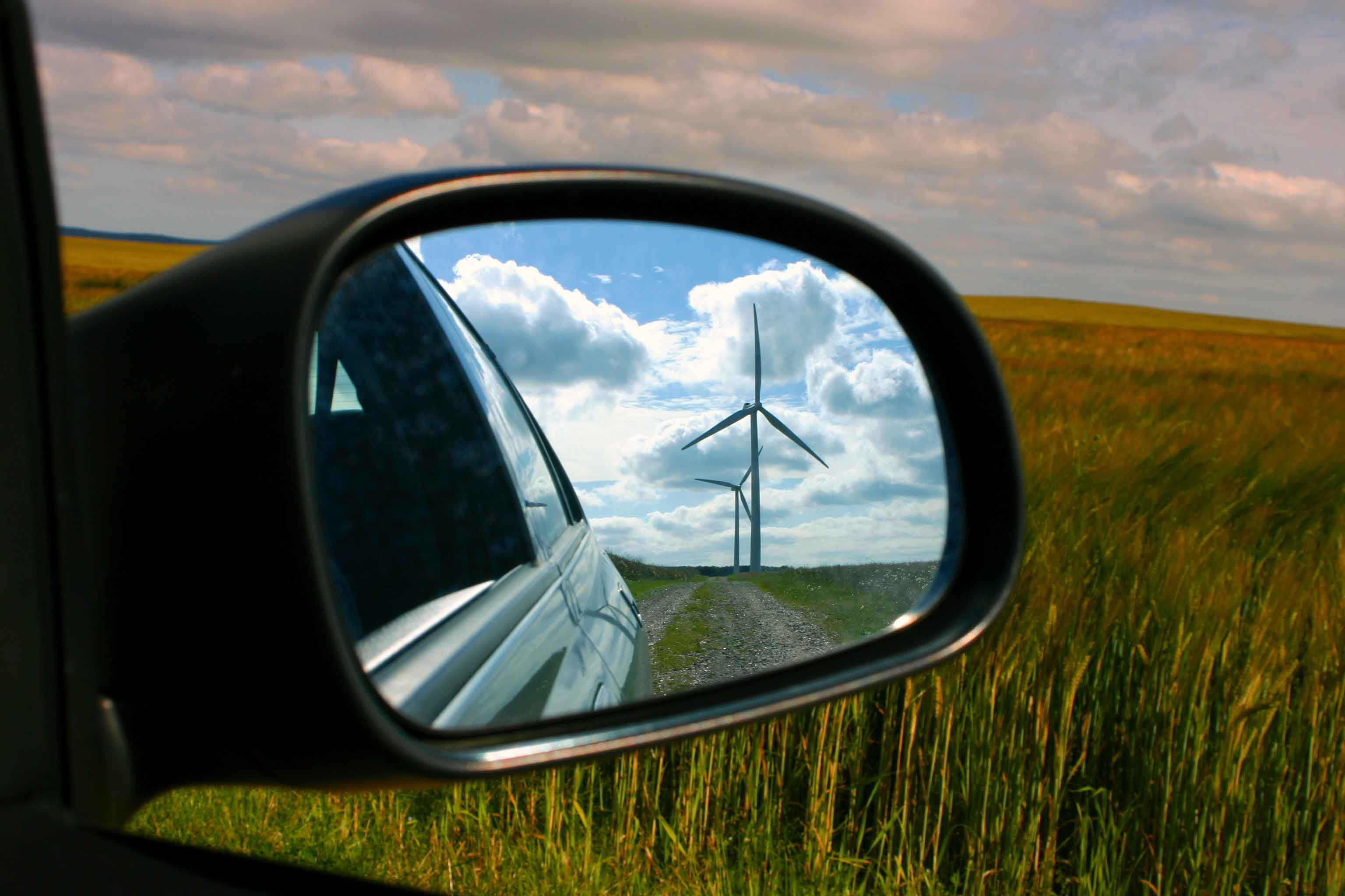 Side mirror of a car with a reflection of wind turbines